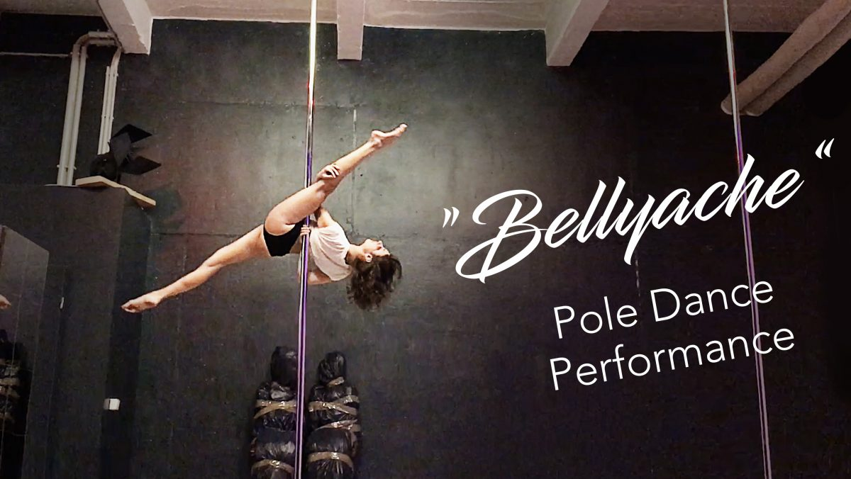 A pole dancer performing a pole split on stage